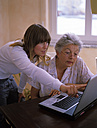 Daughter showing laptop to her mother - DK00085