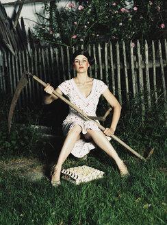 Woman sitting in garden, holding scythe - 00013DK