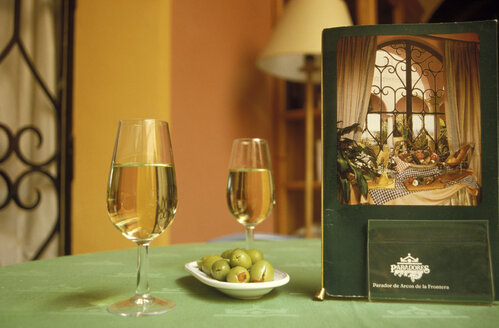 Wine glass with stuffed olives and menu placed on table - 00545MS