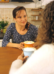 Women sitting with coffee in kitchen - PE00216