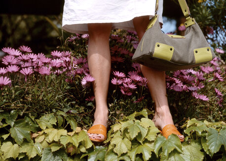 Woman holding handbag, low section - PE00126