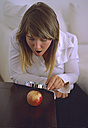 Woman looking at apple through magnifying glass - DK00049