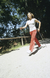 Woman walking with sticks, nordic walking - PEF00364