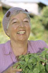 Smiling senior woman holding basil plants, close-up - PEF00325