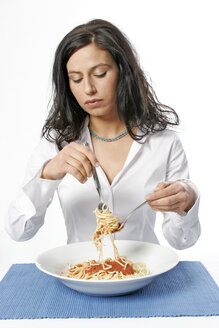 Young woman eating bowl of spaghetti with fork, portrait - LDF00046