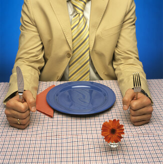 Man sitting at table with empty plate - JLF00019