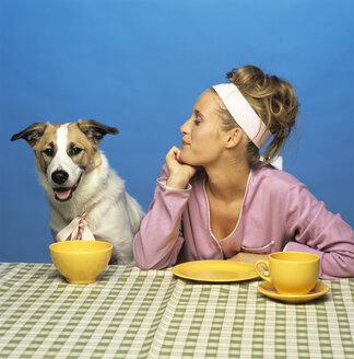 Woman watching dog at table - JLF00014