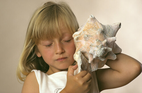 Girl listening to sea shell, close up - CRF00553