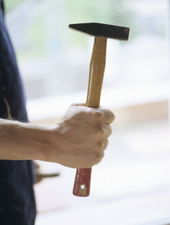 Man holding hammer, midsection - PEF00354