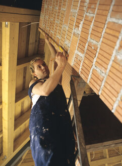 Carpenter measuring wall - PEF00346