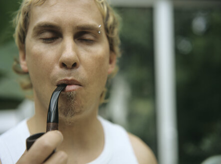 Young man with pipe, eyes closed, close-up - PEF00340