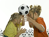 Girls (8-11) balancing soccer ball with head - LMF00027