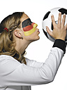Woman with German flag painted on face and wearing German football dress kissing football, close-up - LMF00012