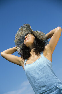 Woman wearing hat with eyes closed, low angle view - LDF00065