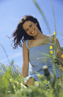 Woman laughing sitting in meadow - LDF00098