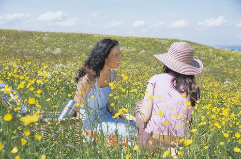 Two women sitting in field - LDF00080