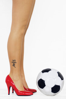 Legs of a woman with red high heels standing in front of a soccer ball - LRF00001