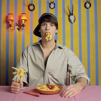 Young man eating French fries - JLF00029