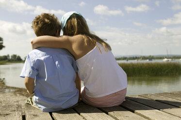 Girl and boy sitting on footbridge, rear view - CKF00102