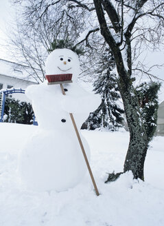 Snowman holding broom by bare tree - PEF00436