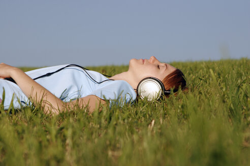Woman lying in grass listening to music - CLF00044