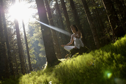 Young woman mediating in forest, low angle view - HHF00133