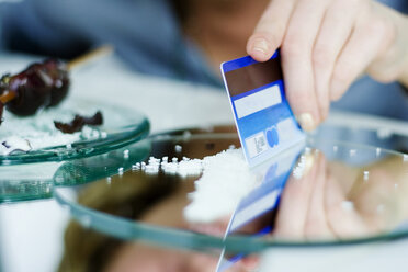 Woman cutting sweets on mirror with credit card, close-up - MFF00020