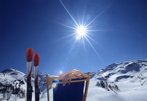 Person sitting in deckchair in alps, winter - HHF00193
