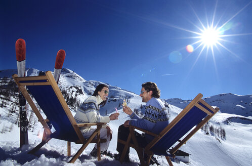 Couple sitting on deckchair in snow toasting glasses, side view - HHF00190