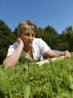 Man reading book lying on grass - DKF00096