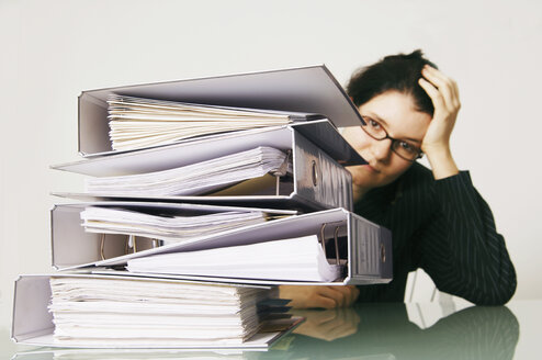Mid adult woman with files on desk head in hands - 00040LRH-U