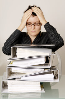 Mid adult woman with files on desk head in hands - 00037LRH-U