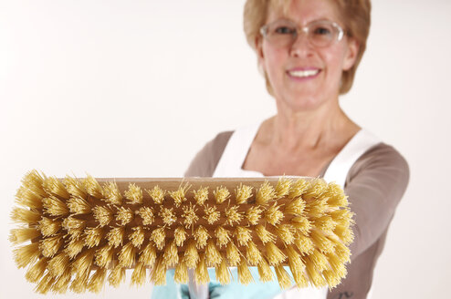 Mature woman holding broom - 00031LRH-U