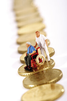Figurine in wheelchair and caregiver on row of coins - 03142CS-U