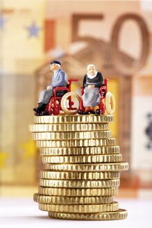 Figurines in wheelchairs on pile of coins - 03139CS-U