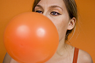 Woman blowing up balloon - MFF00183
