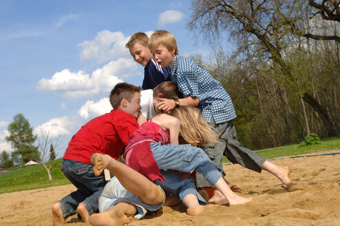 Children (6-9) play fighting on playground - CRF00877