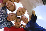 Children (6-9) in huddle, low angle view, portrait - CRF00871