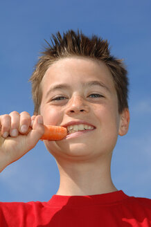 Boy (6-7) eating carrot, low angle view, close-up - CRF00868