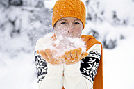Young woman blowing snow, portrait - HH00346