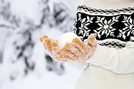 Young woman with snowball, close-up, midsection - HH00342
