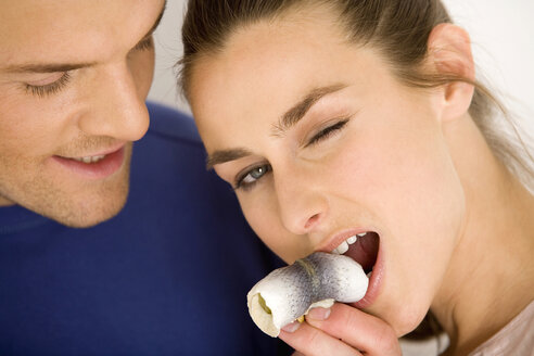 Young couple, woman eating rollmop - WESTF00475