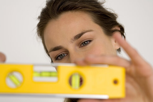 Young woman holding spirit level, close-up - WESTF00472