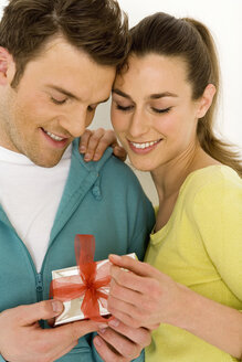 Young couple looking at gift, smiling, close-up - WESTF00513