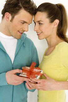 Young couple holding gift, close-up, smiling - WESTF00510
