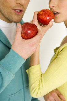 Young couple holding apple, mid section, close-up - WESTF00497