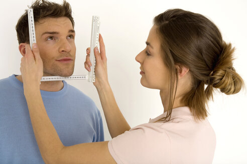 Woman measuring man's face with ruler, smiling, close-up - WESTF00482