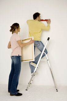 Young couple hanging up painting, man standing on ladder - WESTF00584