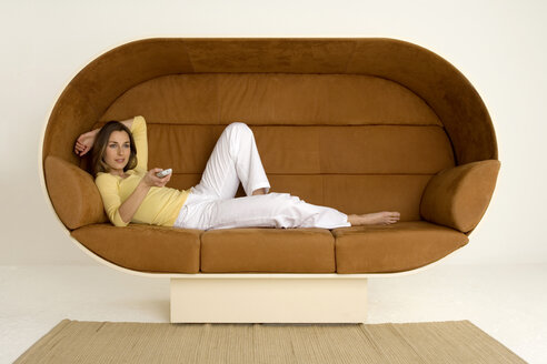Young woman lying on sofa holding remote control, smiling - WESTF00534