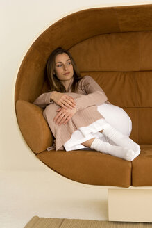 Young woman relaxing on sofa, looking away - WESTF00525